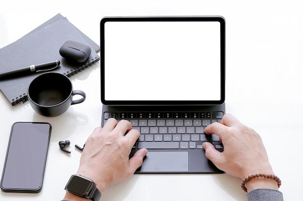 Widok zbliżenie ręki człowieka pracującego na tablecie z klawiaturą