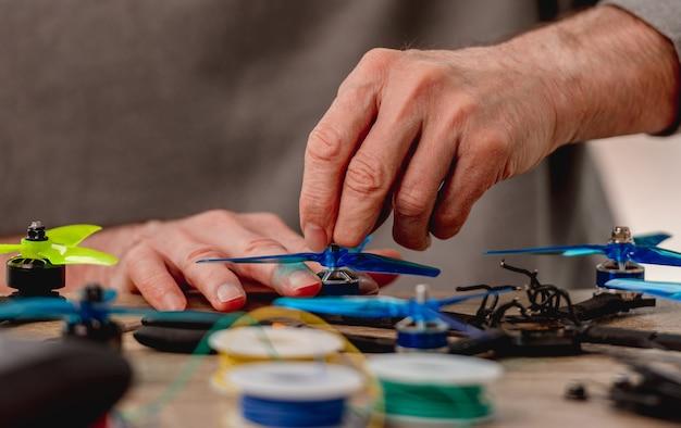 Widok zbliżenie serwisu mężczyzna ręce śruby śmigła quadcoptera z metalową nakrętką