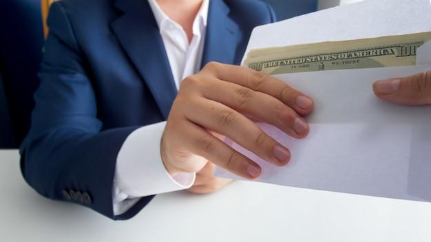 Widok zbliżenie skorumpowanego polityka płci męskiej biorącego łapówkę w kopercie