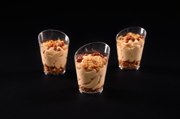 Widok zbliżenie świeżego domowej roboty słodki kremowy deser granola w trzech małych szklankach w rzędzie na białym tle na czarnym tle. smaczny parfait ozdobiony brązowymi kuleczkami na wierzchu i czekoladową bitą śmietaną.