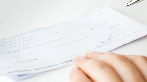 Widok zbliżenie wypełniony i podpisany czek bankowy.