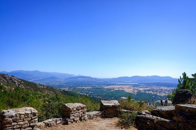 Widok ze średniowiecznej fortecy w dolinie guadarrama w madrycie z górami w tle.