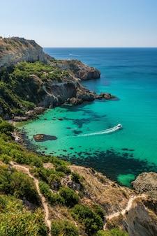 Widok ze szczytu skały na plaży baunty z lazurowym morzem, słoneczny dzień, czyste niebo