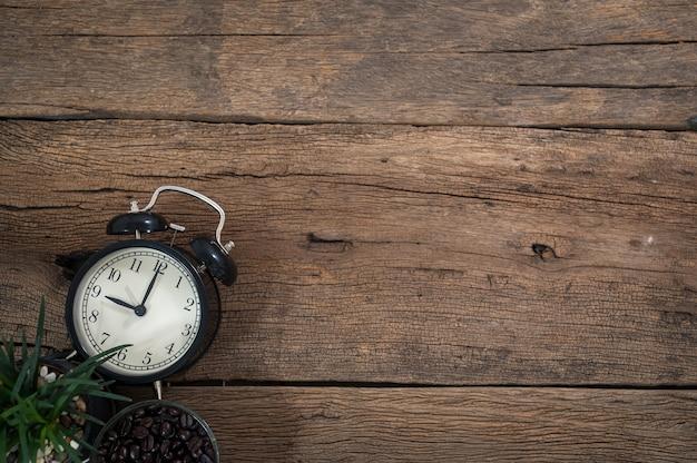 Widok zegara i filiżanki kawy na drewnianym blacie