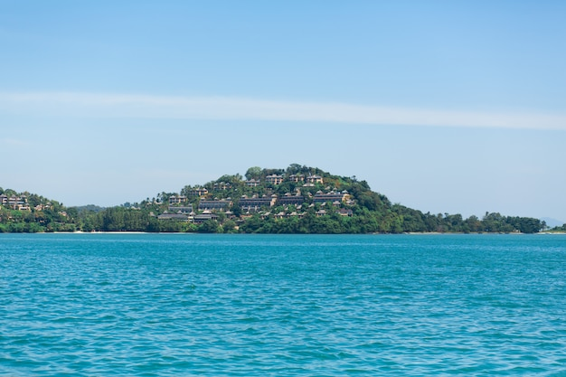 Widok zielona wyspa w błękitnym oceanie. (brak tagów z liniami. max 2 słowa)