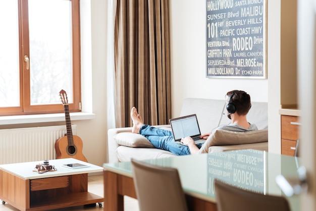 Widok zrelaksowanego młodego mężczyzny słuchającego muzyki z laptopa w domu z tyłu