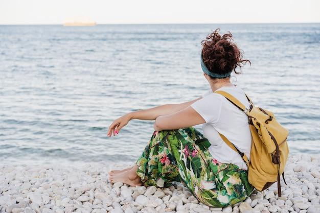 Widok zrelaksowany kaukaski kobieta siedzi przy plaży podczas zachodu słońca na sobie żółty plecak z tyłu. czas letni. marzyć. styl życia na zewnątrz