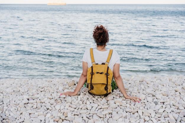 Widok zrelaksowany kaukaski kobieta z żółtym plecakiem siedząc przy plaży podczas zachodu słońca z tyłu. czas letni. marzyć. styl życia na zewnątrz