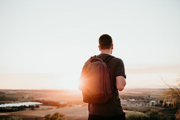 Widok zrelaksowany turysta człowieka z plecakiem o zachodzie słońca w górach z tyłu. piesze wycieczki i przyroda