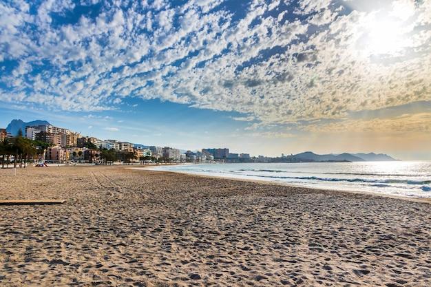 Widoki na plażę villajosa w słoneczny dzień z białymi chmurami, alicante, hiszpania.