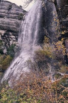 Widoki wodospadu między skałami i drzewami w typowy szary późno jesienny dzień.