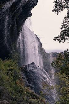 Widoki wodospadu z wodą spadającą na dużą skałę na pierwszym planie