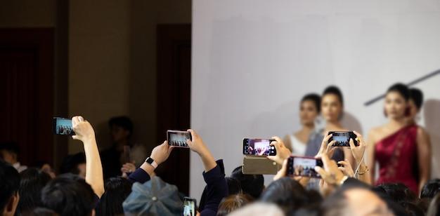 Widownia korzysta ze smartfona, aby zrobić zdjęcie