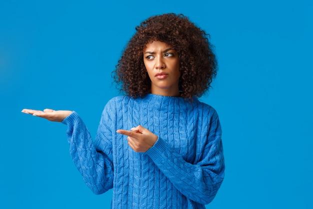 Widzisz to okropnie. niezadowolona smutna i niezadowolona afroamerykańska kobieta mająca najgorszy nowy rok w historii, wskazująca i prezentująca swoje prezenty z brakiem zainteresowania, stojąca zdenerwowana na niebiesko