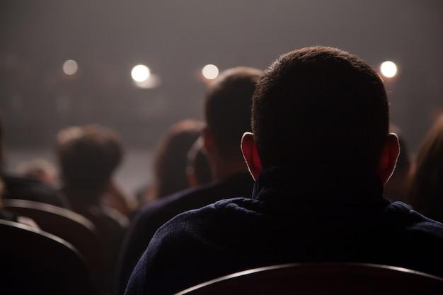 Widzowie czekają na rozpoczęcie koncertu siedząc na krzesłach na widowni.