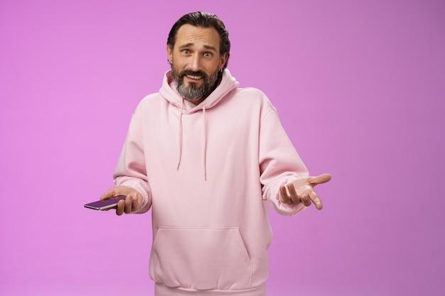Więc co. zdezorientowany, pytający, dorosły, brodaty, stylowy facet w różowej bluzie z kapturem, wzruszający ramionami rozłożonymi na boki konsternacją, trzymający wygląd smartfona nieświadomy nieświadomy aparat nie wie, jak radzić sobie z irytującymi rozmowami telefonicznymi.