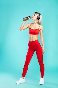 Więc spragniona młoda i wysportowana blondynka w słuchawkach i czerwonym stroju sportowym pije wodę, podczas gdy