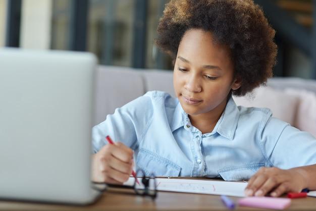 Więcej czasu na sztukę nastoletnia uczennica rasy mieszanej rysująca na papierze kolorowymi markerami podczas nauki