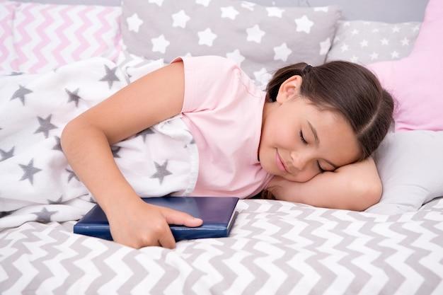 Więcej czytasz, lepiej śpisz. małe dziecko śpi w łóżku. senny czas. pora snu. sen dzieciństwa. zdrowe nawyki snu. zdrowie i opieka nad dziećmi. dobranoc. śpiąca królewna.