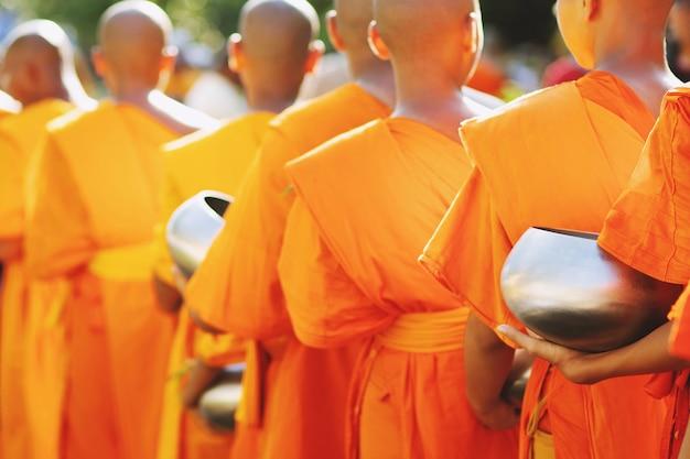 Więcej mnichów trzymających się za ręce daje miskę na jałmużnę, która wyszła z porannych ofiar w świątyni buddyjskiej