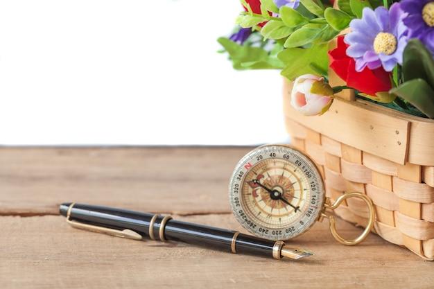 Wieczne pióro i kompas z roślin kwiatowych w koszyku