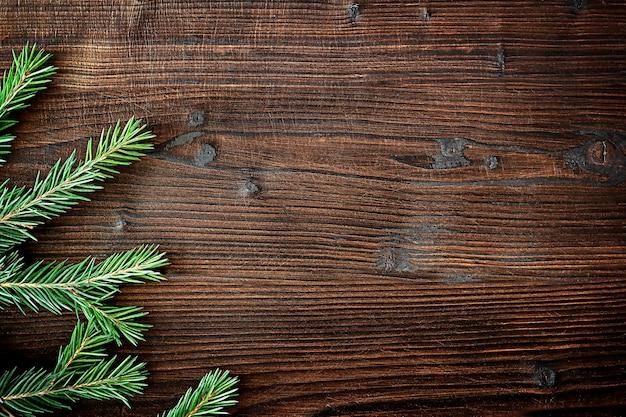 Wiecznie zielone gałęzie jodły na drewnianym tle