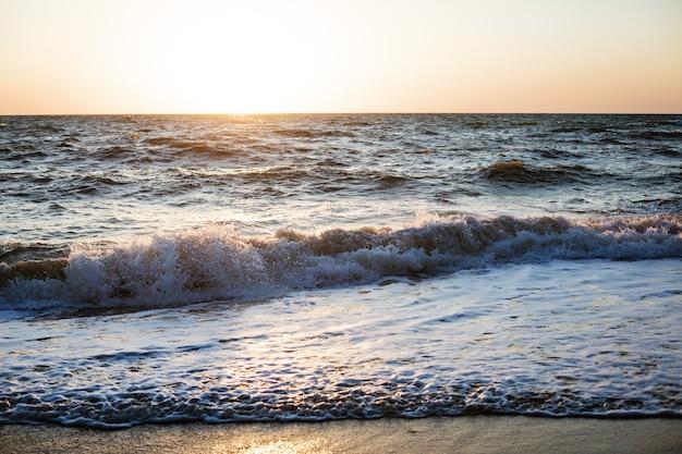 Wieczór ciemne morze błękitne fale zachód słońca piaszczysta plaża miękka fala oceanicznej piany