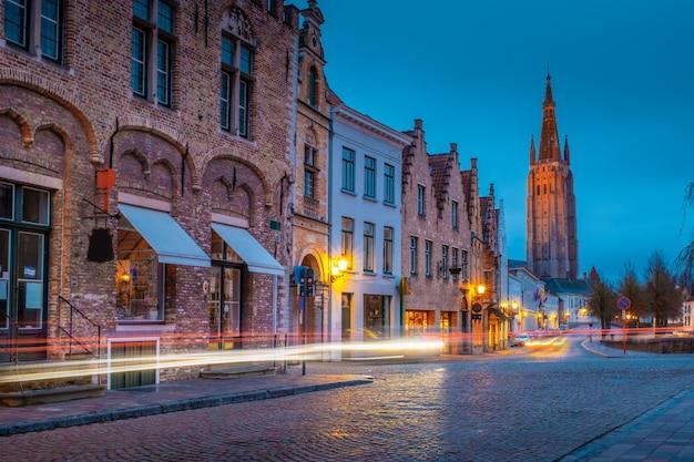 Wieczór na ulicach brugii po deszczu. widok nocy onze lieve. vrouw brugge na tle niebieskiego wieczornego nieba. belgia.