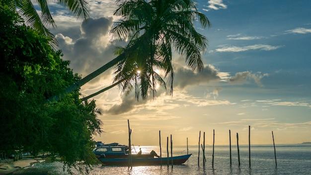 Wieczór na wyspie kri. łodzie leżą pod palmami. raja ampat, indonezja, papua zachodnia