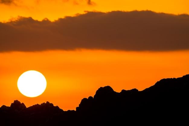 Wieczór nad sylwetką pasma górskiego. wielkie słońce na pomarańczowym niebie