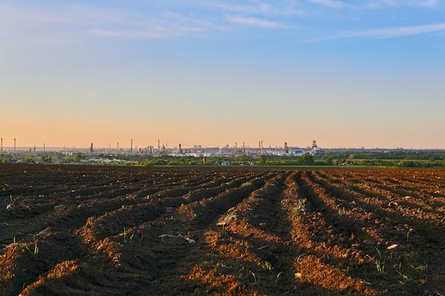 Wieczór wiejski krajobraz z zaoranymi polami i ogromną rafinerią ropy naftowej na horyzoncie