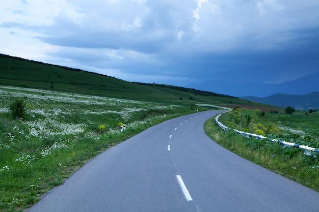 Wieczorem droga asfaltowa schodzi zboczem góry w lesie