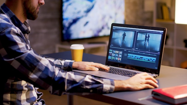 Wieczorem młody twórca treści pracuje nad projektem multimedialnym. twórca treści pracujący na wideo.