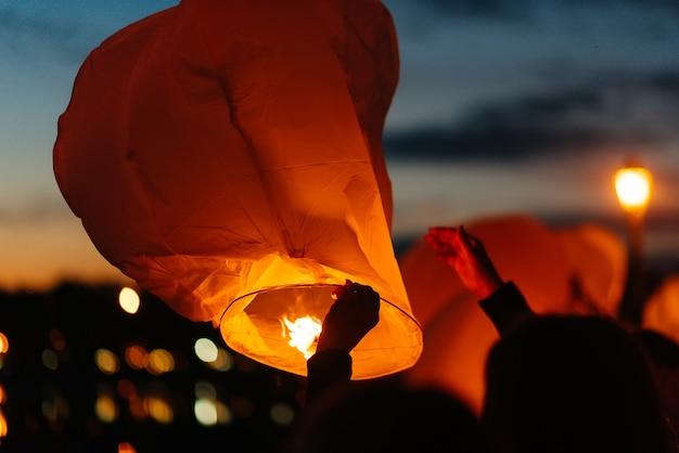 Wieczorem o zachodzie słońca ludzie z bliskimi i przyjaciółmi zapalają tradycyjne lampiony. tradycja i podróże.