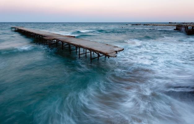 Wieczorna burza na morzu i zrujnowane molo (morze czarne, bułgaria).