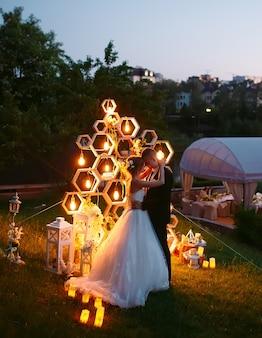 Wieczorna ceremonia ślubna. panna młoda i pan młody są na tle łuku ślubnego.
