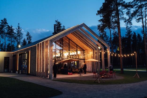 Wieczorna iluminacja na dziedzińcu na tle nowoczesnego drewnianego domu