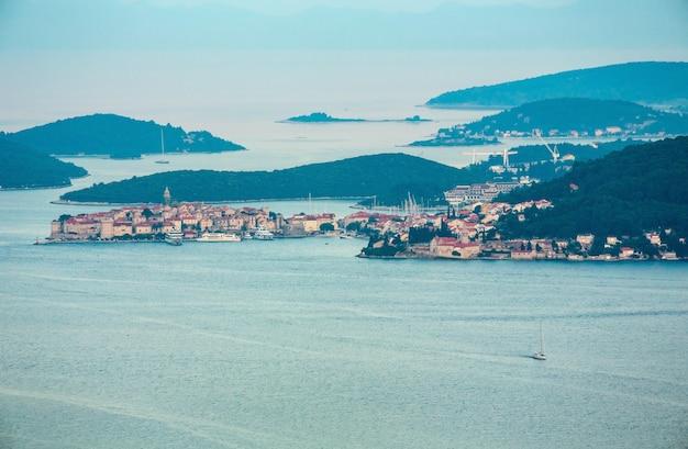 Wieczorne letnie wybrzeże, chorwackie wyspy i miasto korcula na wybrzeżu (widok z półwyspu peljesac, chorwacja).