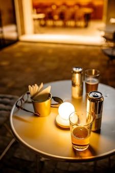 Wieczorne światło na okrągłym stole na letnim tarasie kawiarni z piwem