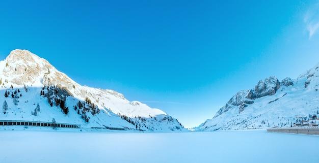 Wieczorne szopy w zimowych górach w pobliżu zamarzniętego jeziora fedaia trentino, prowincja belluno, włochy.