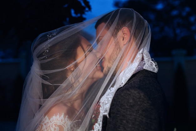 Wieczorne zdjęcie nowożeńców pokrytych welonem