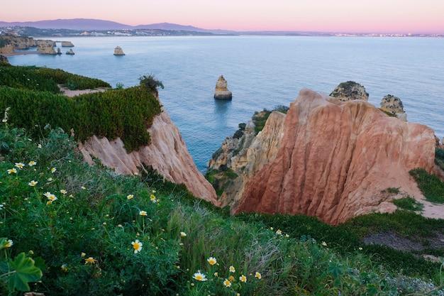Wieczorny krajobraz morski, czerwone urocze skały, plaże i wyspy na wybrzeżu oceanu atlantyckiego w mieście lagos w portugalii