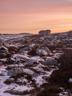 Wieczorny krajobraz polarny ze starym zrujnowanym domem na skalistym brzegu. zimowa teriberka.