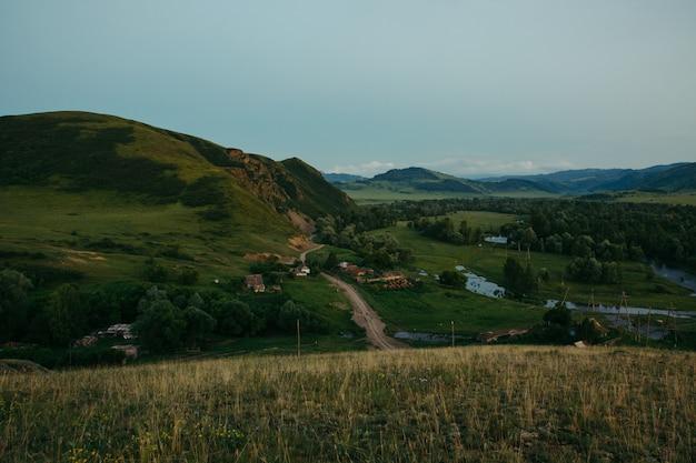 Wieczorny krajobraz wsi zbudowany wśród wzgórz, lasów i gór. otwarta przestrzeń. dzika natura. interakcja z naturą ałtaju.