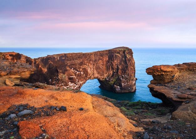 Wieczorny krajobraz z widokiem na skalisty przylądek i ocean