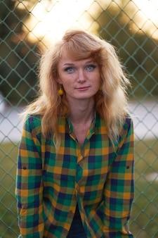 Wieczorny portret rudowłosej dziewczyny ubranej w kraciastą koszulę i stojącej obok ogrodzenia