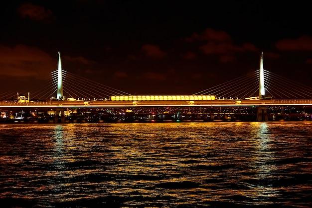 Wieczorny rejs statkiem po bosforze w stambule. most bosforski, w nocy światła.