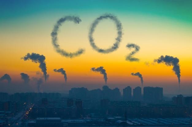 Wieczorny widok na przemysłowy krajobraz miasta z emisją dymu z kominów o zachodzie słońca. napis co2.