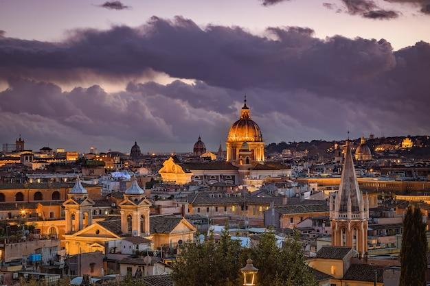 Wieczorny widok na rzymskie dachy z publicznego parku pincian hill, ogrody villa borghese, rzym, włochy