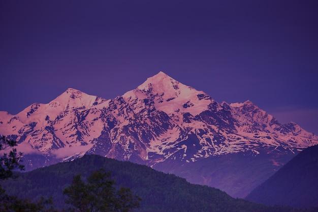 Wieczorny widok na zachód słońca nad ośnieżonym szczytem. krajobraz przyrody. dramatyczna scena pochmurna. wakacje, podróże, sport, rekreacja. główny grzbiet kaukaski, swanetia, gruzja. retro fioletowy filtr tonujący